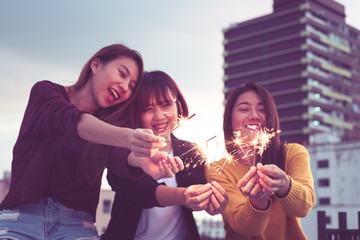 Happy group of asia girl friends enjoy and play sparkler at roof top party at evening sunset,Holiday celebration festive,teenage lifestyle,freedom and fun.