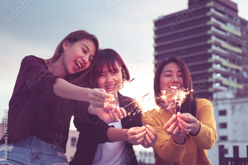 Foto Murales Happy group of asia girl friends enjoy and play sparkler at roof top party at evening sunset,Holiday celebration festive,teenage lifestyle,freedom and fun.