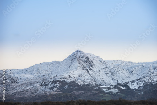 Fotobehang Blauwe hemel Beautiful Winter sunrise landscape image of Mount Snowdon and other peaks in Snowdonia National Park