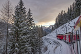 Red train in the snow in swiss alps - 187098987