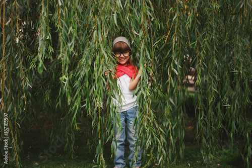 little girl hiding in the willow foliage