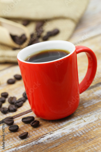 Black coffee in red mug on rustic wooden surface and scattered roasted coffee beans