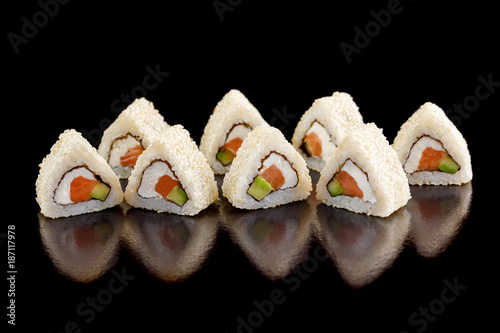 Foto op Canvas Sushi bar Original sushi rolls with salmon, cream cheese and avocado on a black background.