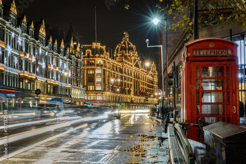 Fridge magnet traffic jam in street of London at night during christmas holidays with a historical phone cab