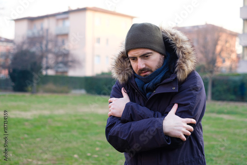 Foto Murales Man dressed in warm clothes feeling cold