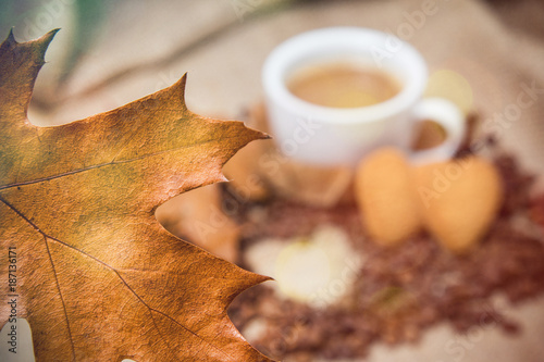Coffee with milk and a heart-shaped cookie on a coarse cloth in beige tones
