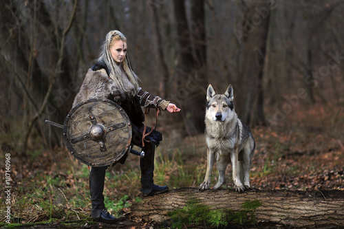 Beautiful viking warrior woman in traditional warrior clothes, with ax and shield, next to an wild wolf, animal