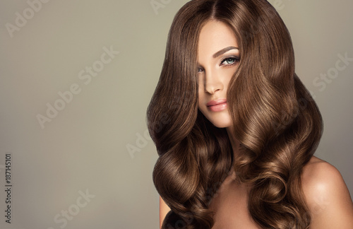 Deurstickers Kapsalon Beautiful model girl with long wavy and shiny hair . Brunette woman with curly hairstyle