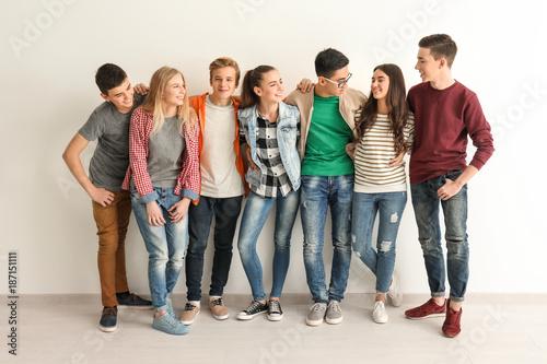 Group of cute teenagers near white wall