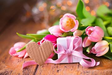 Tulpen, kleines Geschenk und rustikales Herz aus Pappe mit Textfreiraum