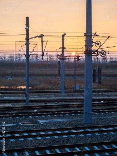 In de dag Spoorlijn Schienen mit Oberleitung an der Ostbahn mit Sonnenaufgang