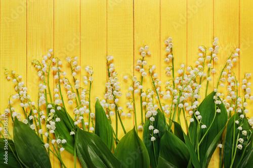 Fotobehang Lelietjes van dalen Spring flowers Lily of the valley in yellow wooden background.