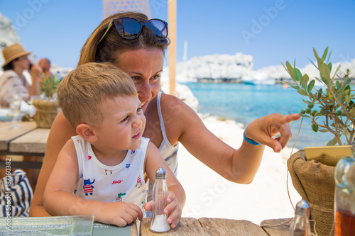 Mother and her little boy sitting on legs at open restaurant