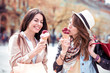 Two beautiful girls eating ice cream and shopping.
