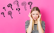 Question Marks with young woman feeling stressed on a pink background