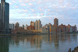 Urban landscape at sunset in winter along East River in Manhattan, New York. Buildings reflection in harmony with pastel hues of cumulus clouds during the quiet city sunset.