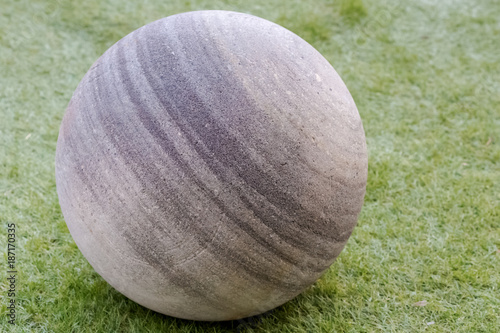 Staande foto Bol boule de pierre sur pelouse