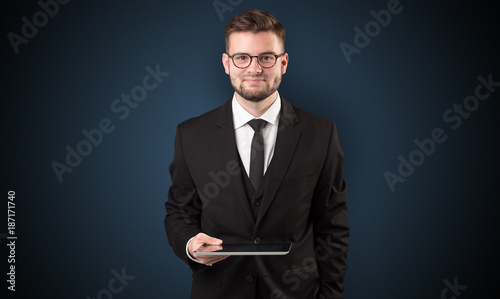 Businessman holding tablet with dark background
