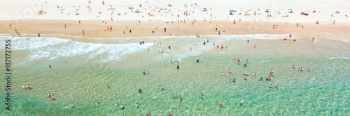 People swimming at the beach in summer with blue water from an aerial perspective - 187172755