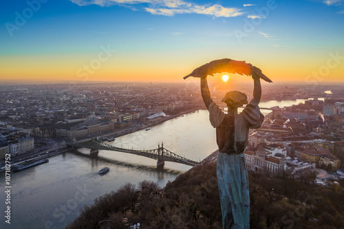 obraz lub plakat Budapest, Hungary - Aerial panoramic sunrise view at the Statue of Liberty with Liberty Bridge and sightseeing boat on River Danube taken from Gellert Hill