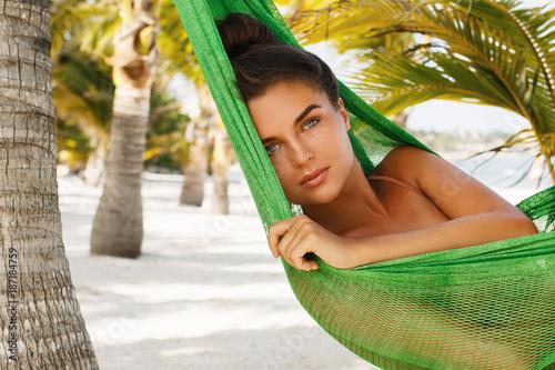 Foto Murales Happy and beautiful woman lying in the hammock