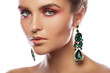 Beautiful woman with a colorful makeup is wearing earrings with green emeralds