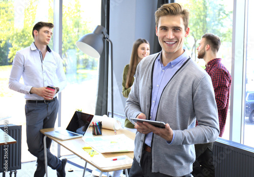 Poster Smiling young man using digital tablet in the office.