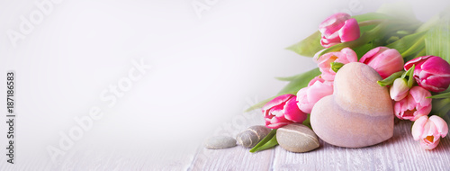 Beautiful tulips with stone heart on light wooden background