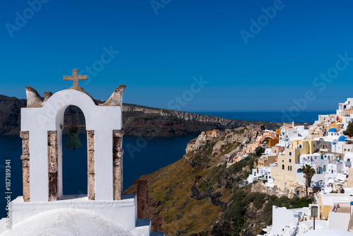 Santorini, Greece. View of sea surface through traditional Greek white church arch with cross and bells in Oia village of Cyclades Island, Santorini, Greece. - 187189341