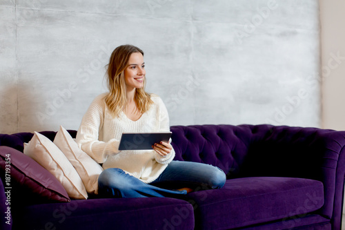 Young woman with tablet on sofa