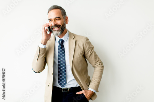 Poster Handsome mature businessman with mobile phone in the office