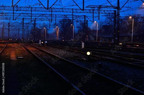Fotobehang Nacht snelweg Tory kolejowe, semafory, sygnalizatory wieczorem i lekka mgła/
