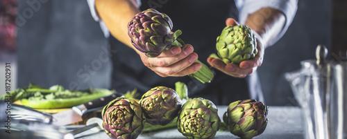 Poster Chefkoch in der Küche mit Frischem Gemüse(Artischocken)