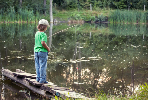 Happy boy go fishing on the river, one children fisherman with a fishing rod on the shore of lake