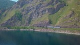 ProRes. Vintage, historic steam train passes through the mountains along the shore. - 187204394