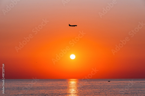 Poster Oranje eclat Summer. Sea. Sunset on the Black sea. Sochi. Krasnodar Krai. Russia. The plane in the sky.
