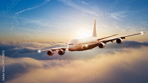 Huge commercial airplane flying above clouds