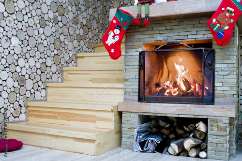 Fireplace with Christmas decorations. The firewood is burning in the fireplace.