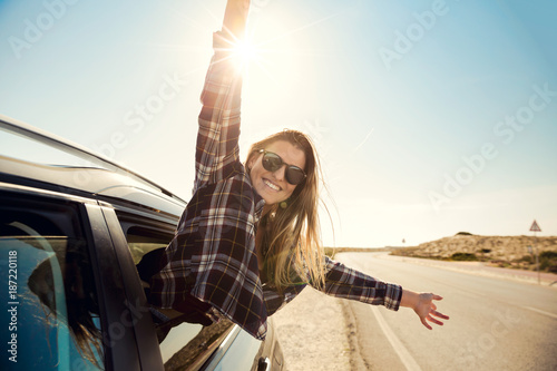 Foto Murales happy girl looking out the car window