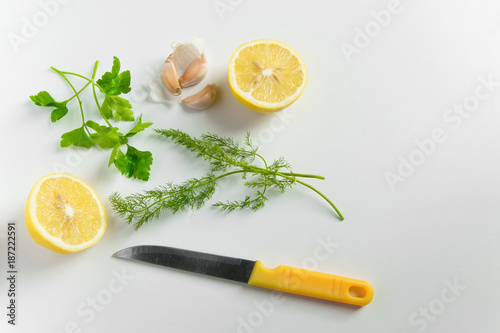 Top view of fresh ingredients for healthy cooking condiments - lemon, garlic, green onion and fennel on white background with space for text. Healthy eating concept