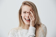 Headshot of cute woman with dark eyes, blonde long hair, happy gentle smile rejoicing her success. Cheerful woman having birthday having pleased expression and pleasure. Face expressions