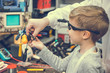 Little boy and his teacher making experiment with magnet and work tools.