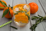 Detox water with mandarins and rosemary on the grey wooden background