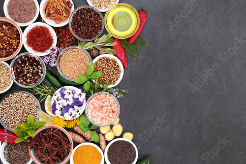 Fresh and dried herb and spice selection with edible flowers and olive oil forming an abstract border on slate background.