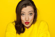 beautiful sexy woman in a yellow blouse with kissing gesture on a yellow background