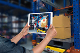 Industrial 4.0 , Augmented reality and smart logistic concept. Hand holding tablet with AR application for check order pick time around the world and supply chain in smart factory background.