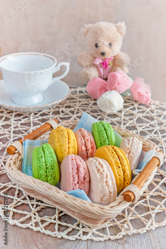 Poster Macarons Freshly baked macarons in a wicker basket with marshmallows and a Cup of tea.