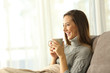 Pensive woman holding a coffee mug relaxing at home