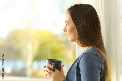 Profile of a woman looking through a window