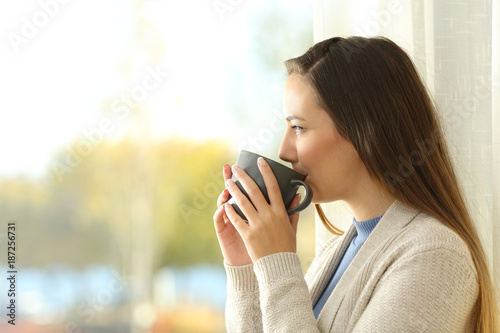 Lady drinking coffee and looking through a window